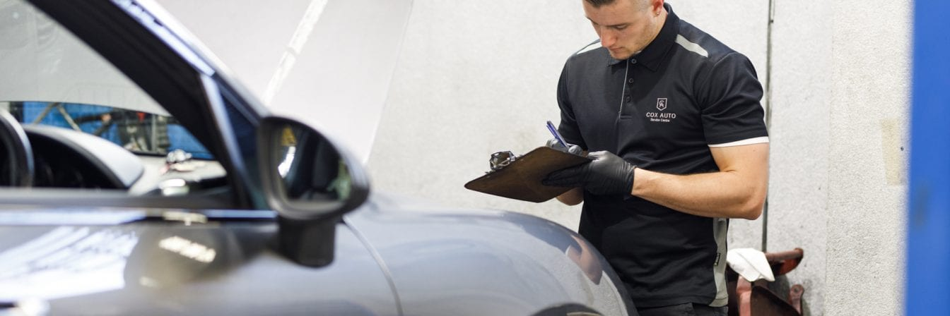 Cox Auto employee inspecting a car